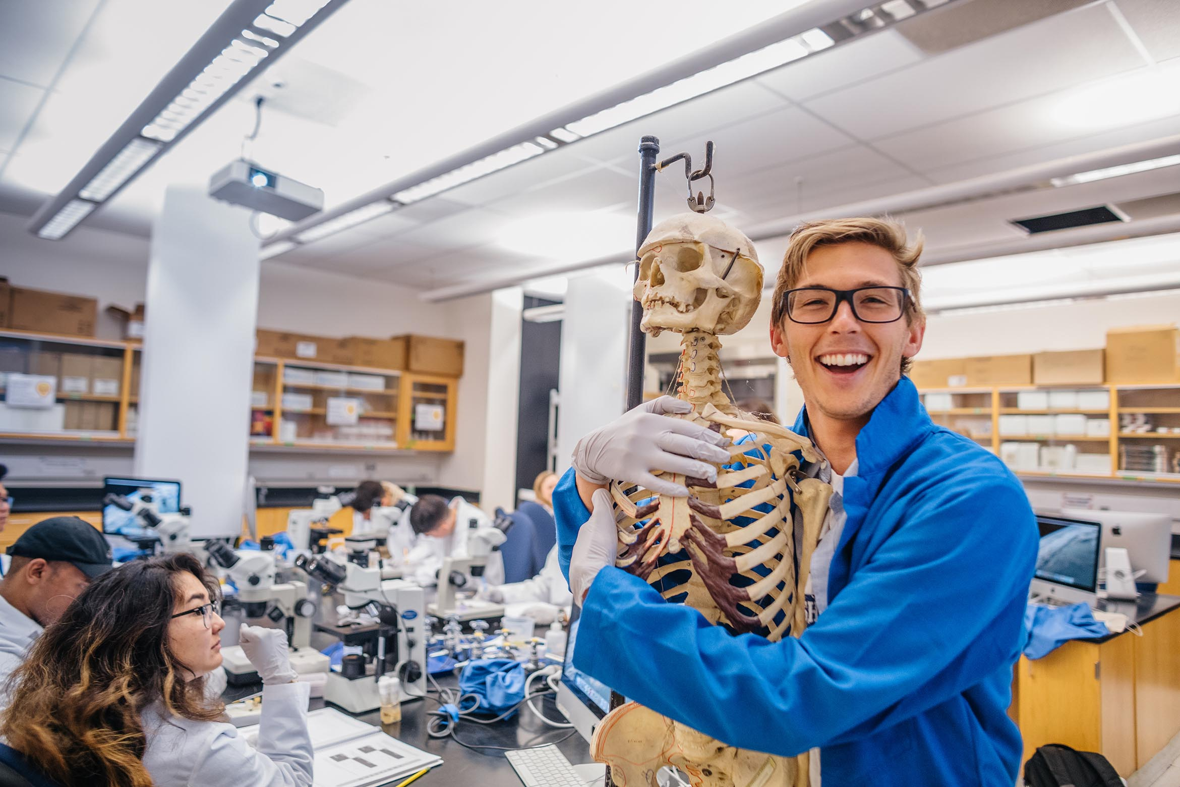 This is a student in a lab coat hugging a skeleton.