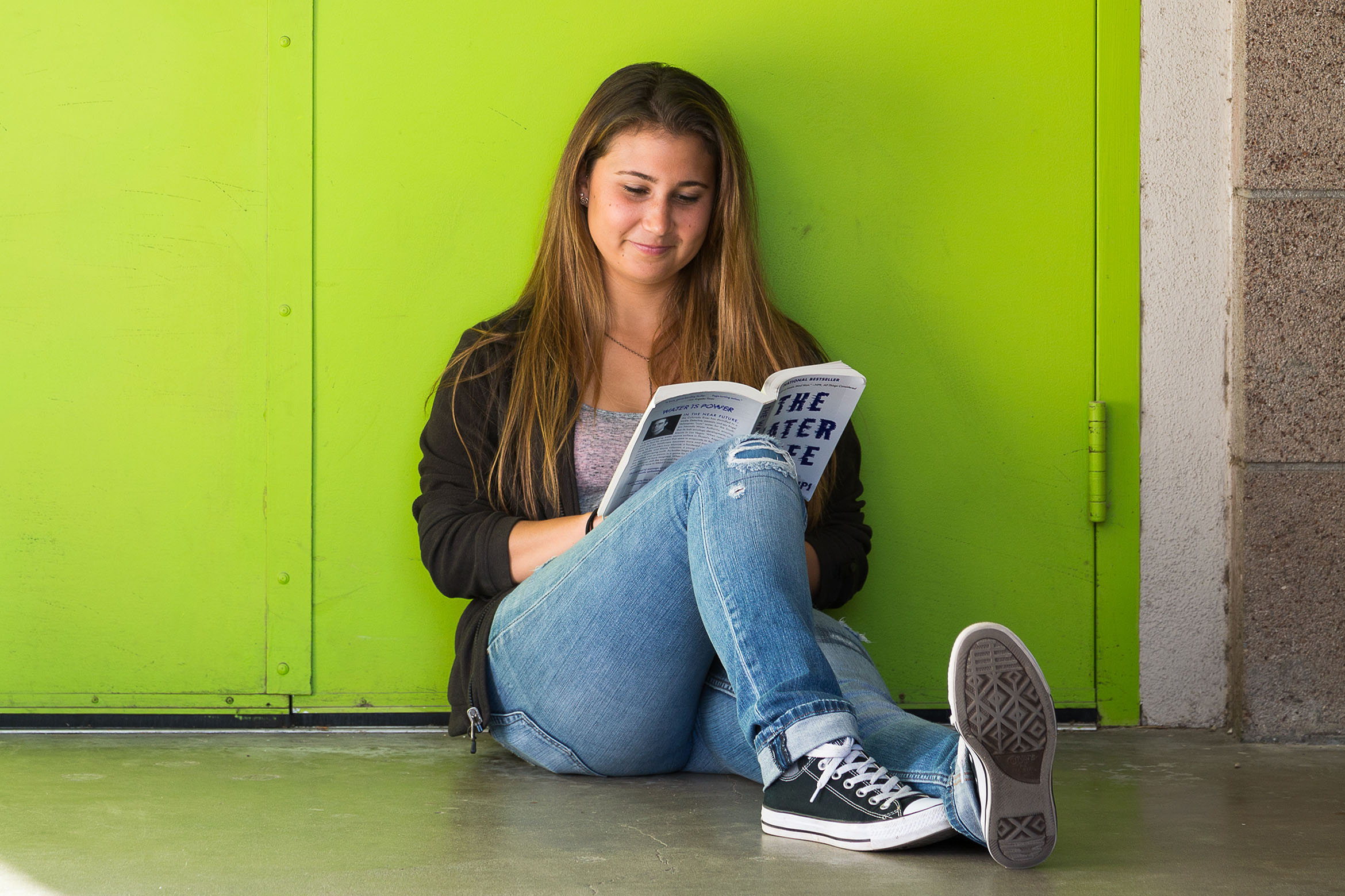 This is a student reading a book against a green wall.