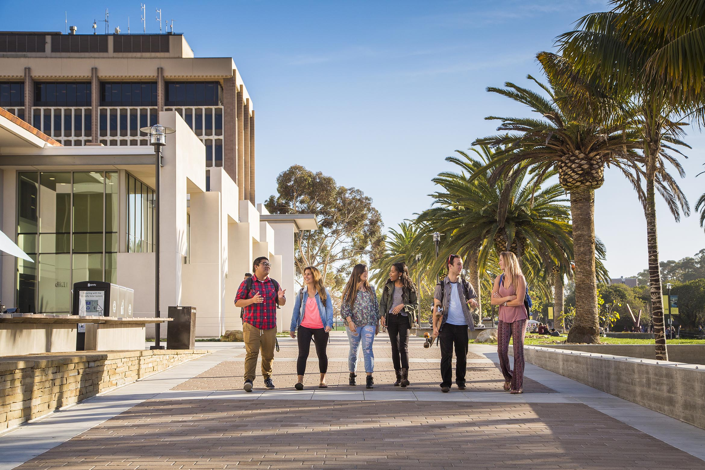 Six students in pairs converse as they walk in front of the library.