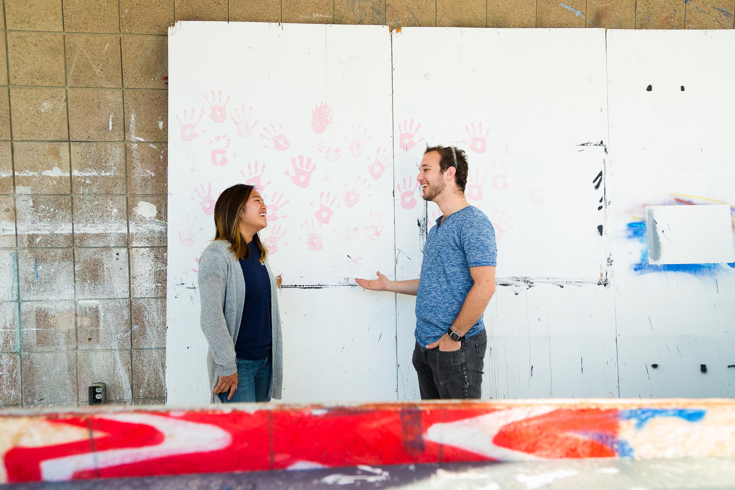 This is an image of two students chatting in front of an art mural.